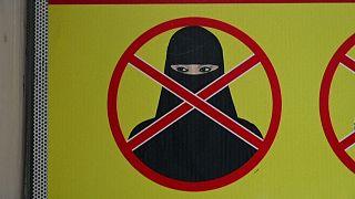لافتة على أحد المحلات التجارية تمنع دخول النساء المنقبات