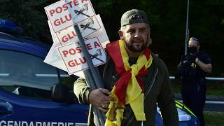 A protester holds a sign as he takes part in a demonstration of hunters to denounce the ban on glue hunting, in Prades, southwestern France, on Septembre 12, 2020