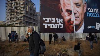 فلسطينيون ينتظرون المواصلات تحت لوحة إعلانية لحملة الانتخابات الإسرائيلية. 2021/03/14