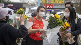 Roula AbiSamra, center, and Chelsey (last name withheld), right, prepare to lay flowers bouquets at a makeshift memorial outside of the Gold Spa in Atlanta, Wednesday.