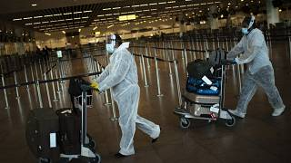FILE - In this July 29, 2020 file photo, passengers wearing full protective gear push their luggage in the departure hall of Zaventem international airport, Belgium