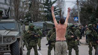 """جندي أوكراني في القرم عارياً أمام جنود شاعت تسميتهم بـ""""الجنود الخضر"""" يعتقد أنهم تابعون لروسيا"""