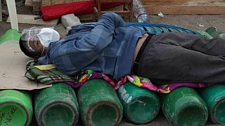 Um homem dorme sobre garrafas de oxigénio, um bem escasso agora no Peru
