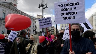 "A man holds a placard reading ""I decide when and how to die"" during a demonstration in support of a law legalising euthanasia in Madrid on March 18, 202"
