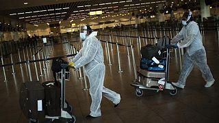 مسافران يرتديان ملابس واقية ضد فيروس كورونا داخل صالة المغادرة بمطار زافينتيم الدولي في العاصمة البلجيكية، بروكسل بتاريخ 29 تموز/يوليو 2020