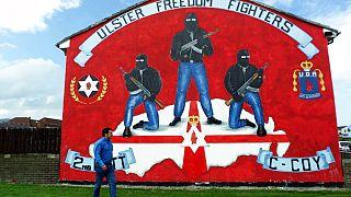 Ein Mann vor einem Mural-Wandbild der Untergrundbewegung Ulster Defence Association (Unionisten)