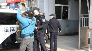Security officers stand guard as a police van arrives at a court building in Dandong in northeastern China's Liaoning Province, Friday, March 19, 2021.