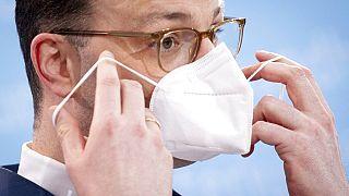 Der deutsche Gesundheitsminister Jens Spahn setzt sich nach einer Pressekonferenz seine FFP-2 -Maske auf