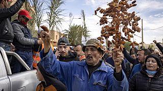Un agriculteur portant une branche de dattes lors de la manifestation de Figuig, Maroc, 18 mars 2021