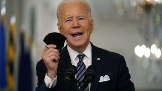 الرئيس الأميركي جو بايدن رافعاً الكمامة خلال مؤتمر صحافي في البيت الأبيض