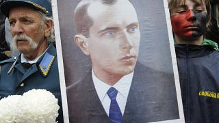 A man dressed in Ukrainian insurgent army uniform seen by a young supporter of the Ukrainian Insurgent Army holds a portrait of Stepan Bandera.