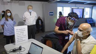 رئيس الوزراء البريطاني بوريس جونسون يحضر عملية تلقيح مريض بلقاح أكسفورد أسترا زينيكا.