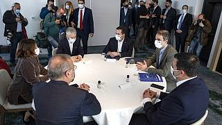 Greece's Prime Minister Kyriakos Mitsotakis, right, attends a ministerial meeting in Athens, Saturday, March 20, 2021.