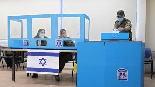 جندي إسرائيلي يدلي بصوته في قاعدة عسكرية بالقرب من بلدة كفر قرع العربية، وسط إسرائيل.