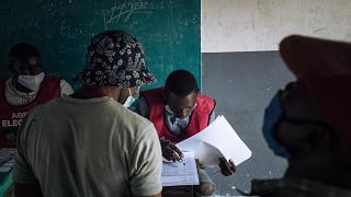 An electoral commission official checks the voters roll at a polling station in Brazzaville, Congo, on March 21, 2021.
