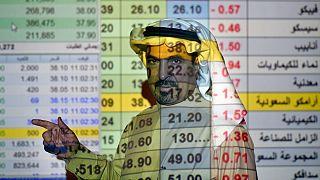 یک کارگزار بورس عربستان در حال توضیح در مورد روند قیمت سهام شرکتها از جمله آرامکو
