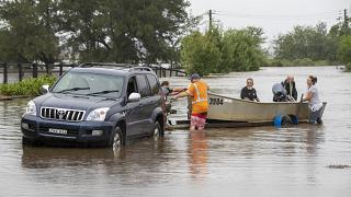 A boat is loaded back onto its trailer on a flooded road at Old Pitt Town, north west of Sydney, Australia, Sunday, March 21, 2021.