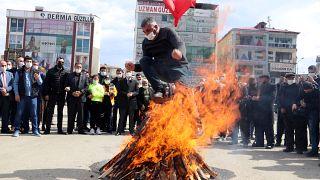 Iğdır'da Nevruz ateşinin üzerinden atlayan bir kişi