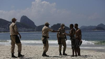 Police work to keep beachgoers off the Arpoador beach which is closed due to reinstated COVID-19 pandemic restrictions in Rio de Janeiro, Brazil, Saturday, March 20, 2021.