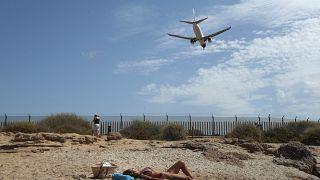 Eine Urlauberin sonnt sich an der Playa del Palma  auf Mallorca. Der nahegelegene Flughafen Son Sant Joan ist dort ziemlich allgegenwärtig