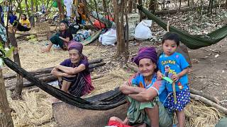 In this photo released by the Free Burma Rangers, Karen women sit with family members in the jungles of northern Karen State, Myanmar.