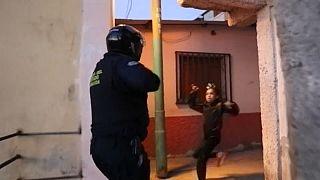 Un policía apunta con un arma a una niña en un operativo para hacer cumplir las medidas contra la COVID-19.