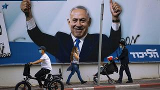 People pass an election campaign billboard for the Likud party that shows a portrait of its leader Prime Minister Benjamin Netanyahu, in Ramat Gan, Israel, , March 21, 2021