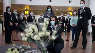 Representatives of victims and others carry flowers and photos at Brussels Airport