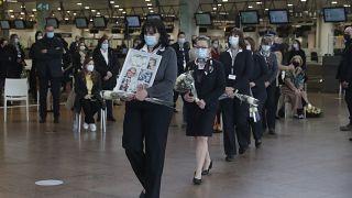 ممثلو الضحايا وغيرهم يحملون الزهور والصور في مطار بروكسل خلال فعاليات الذكرى الخامسة لهجمات بروكسل الإرهابية ، في بروكسل ، الاثنين 22 مارس 2021.