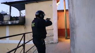 Agente da polícia com arma apontada entra num corredor de uma favela em Los Teques