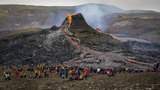 Hikers look at the lava flowing from the erupting Fagradalsfjall volcano, 40 km west of the Icelandic capital Reykjavik. March 21, 2021