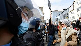 "A woman speaks to police officers on duty at a rally under the motto ""Free citizens Kassel - basic rights and democracy"" in Kassel, Germany, Saturday, March 20, 2021."