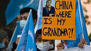 """شاب من أقلية الإيغور يحمل لافتة كتب عليها """"الصين أين جدتي ؟ خلال مظاهرة يوم 1 سبتمبر 2020 أمام مبنى  وزارة الخارجية في برلين"""