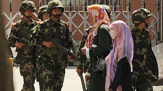 نساء مسلمات من الإيغور يسرن أمام الشرطة الصينية شبه عسكرية في أحد شوارع أورومتشي، عاصمة منطقة شينجيانغ الصينية.