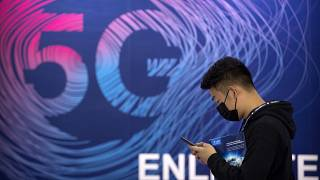 رجل يمر حذو لوحة إشهارية لخدمة 5جي في معرض في بيكين. 2020/09/14