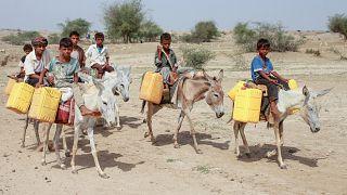 أطفال يمنيون يركبون الحمير لملء صفائح المياه من صهريج في مخيم مؤقت للنازحين في محافظة حجة الشمالية.