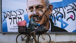 Mann vor einem Wahlplakat mit der Abbildung Netanjahus