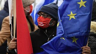 A demonstrator wearing a protective face mask reading 'stop Erdogan' takes part in Brussels