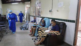 Varios enfermos de COVID-19 sin camas son tratados en los pasillos de un hospital en San Lorenzo, Paraguay.