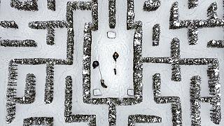 Menschen spazieren mit ihren Hunden in einem schneebedeckten Gartenlabyrinth in Gelsenkirchen, 10.02.2021