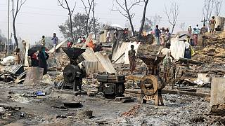 Rohingya refugees stand by remains of Monday's fire at a refugee camp in Balukhali, southern Bangladesh, Tuesday, March 23, 2021.