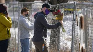 Kiefer Johnson places a bouquet of flowers into a makeshift fence put up around the parking lot outside a King Soopers grocery store where a mass shooting took place.