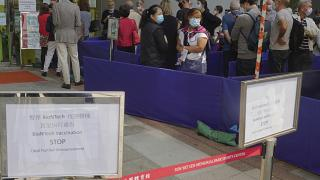 People queue up outside a vaccination center for BioNTech in Hong Kong Wednesday, March 24, 2021.