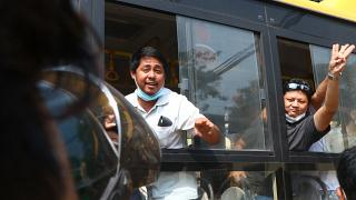 An arrested protester flashes the three-fingered salute while onboard a bus getting out of Insein prison to go to an undisclosed location on March 24, 2021 in Yangon, Myanmar