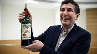 Philippe Darriet, Director of the Oenology Research Unit Institute of Vines, Science and Wine (ISVV) holds a bottle of Petrus that has spent months in space