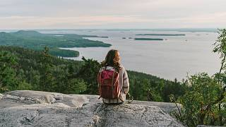Scenic view of woman looking at lake in Finland at sunset.