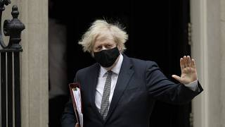 British Prime Minister Boris Johnson waves at the media as he leaves 10 Downing Street for the Houses of Parliament, in London, Wednesday, March 24, 2021.