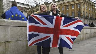"""Brexit supporters hold the Union Jack with a text reading """"Goodbye EU"""" as they celebrate next to a person wearing the EU flag in London, Friday, Jan. 31, 2020."""