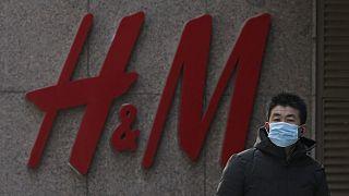 """رجل يقف بجوار أحد متاجر """"إتش أند إم"""" للأزياء السويدية في العاصمة الصينية بكين، 25 آذار/مارس 2021"""