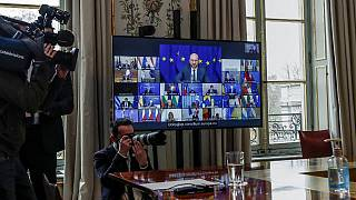 Journalists work as European Council President Charles Michel is seen on a screen during a European Union summit
